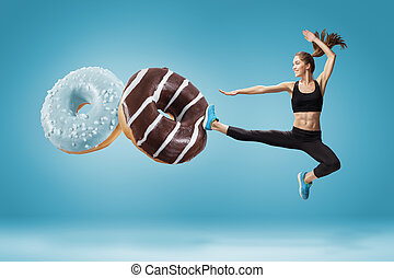 Fit young woman fighting off bad food on a blue background -...
