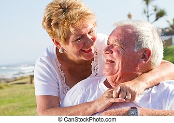 senior couple laughing outdoors and looking into each others...