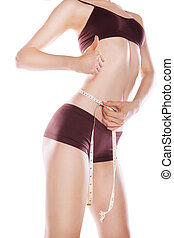 Woman measuring her waist by metric tape isolated
