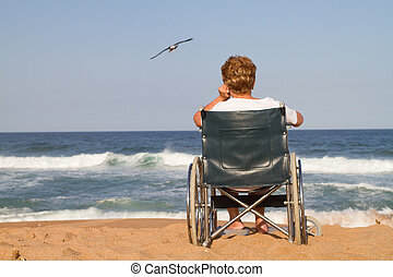 lonely woman in wheelchair on beach - view from behind - she...