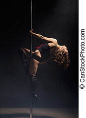Young slim pole dance woman exercising over dark background
