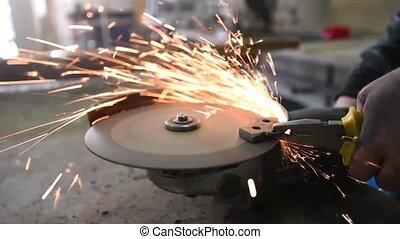 Worker with Angle Grinder does Metalworking in Industrial...