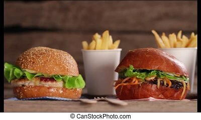 Burgers and french fries. Junk food on wooden background....