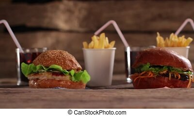 Burgers with beverages and fries. Tasty junk food on table....