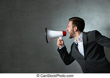 Young businessman with a megaphone - Young handsome shouting...
