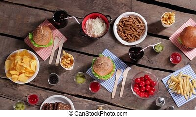 Chips with burgers and beverages Wooden table with different...