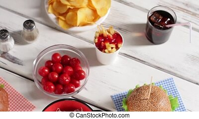 Potato chips and cherry tomatoes White wooden table with...