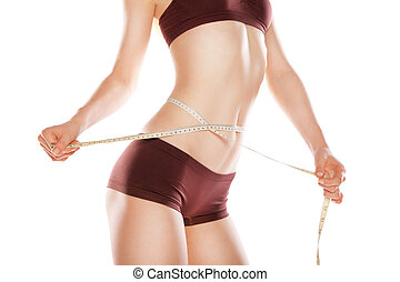 Athletic woman measuring her waist by metric tape - Athletic...