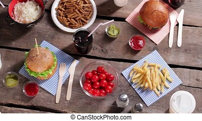 Burger with sauce and fries Knife and fork beside burger...