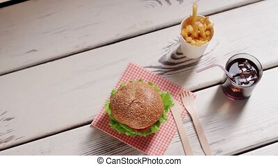 Hamburger with cutlery and drink.