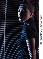 Sexy woman looking through window with jalousie