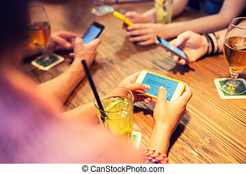 close up of hands with smartphones at restaurant - leisure,...