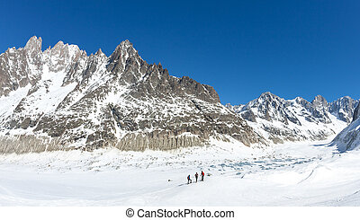 A group of skiers look at Leschaux Glacier, in the Mont Blanc massif, the highest mountain in Europe.