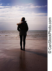 Back of a young woman standing on the beach looking out to sea