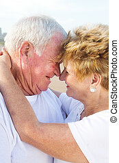 tender loving senior couple on beac