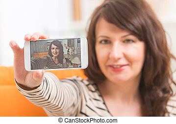 Woman taking selfie picture - Mature attractive woman taking...