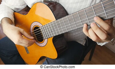 Musician playing a classical guitar in slow motion