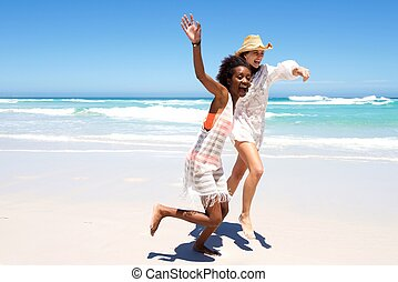 Two female friends running on beach together