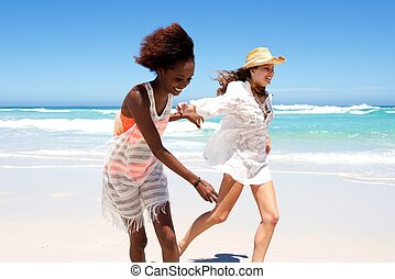 Happy young female friends running on beach