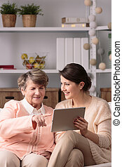 Using the new technology - Senior smart woman using new...