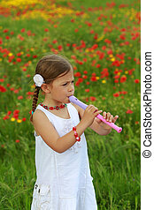 Pretty young girl playing the recorder next to a poppy field