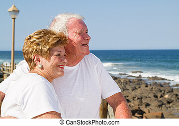 happy senior couple on beach smiling and hugging