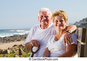 happy senior couple on beach bench smiling and hugging