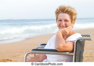 happy woman in wheelchair on beach - a happy smiling woman...