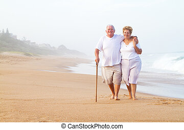 senior couple walking on beach - a senior couple walking on...