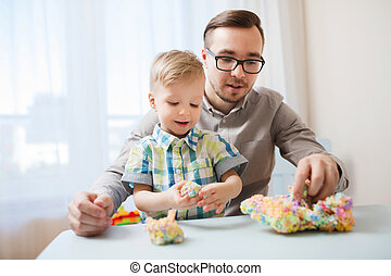 father and son playing with ball clay at home - family,...