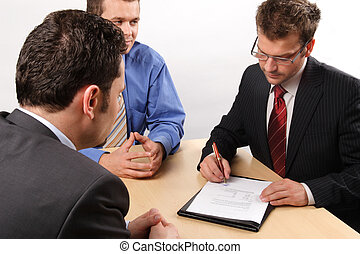 Businesspeople signing a contract - Businesspeople...