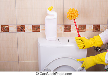 Woman cleaning toilet bowl - Woman with safety gloves...