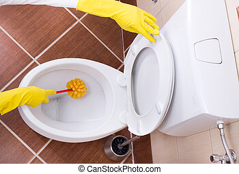 Woman cleaning toilet bowl - Woman with protective gloves...