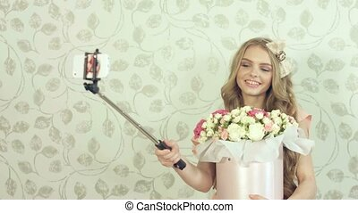 Cute girl with a large bouquet of roses doing selfie using a monopod in the studio