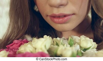 Dreamy girl sniffs a huge bouquet of roses - Dreamy and...