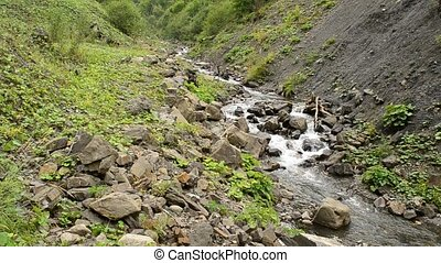 Water stream in mountains flows between rocky hills in summer