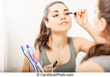 Young brunette putting on mascara