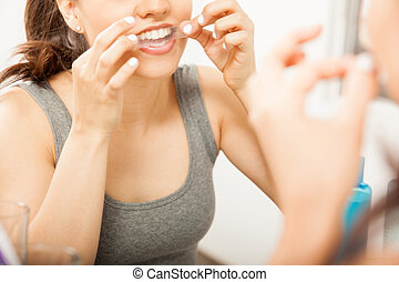 Putting a whitening strip on her teeth - Closeup of a cute...
