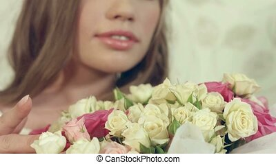 Portrait of beautiful girl posing with a big bouquet of delicate roses