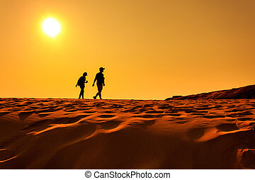 Two people walking on sand desert