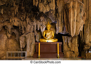 Golden Buddha statue in cave