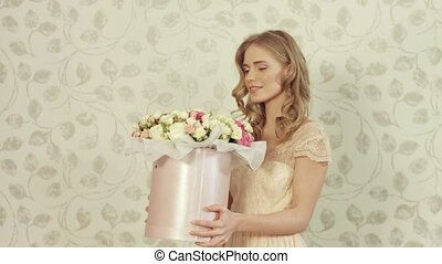 Happy sweet girl with a big bouquet of roses in a box