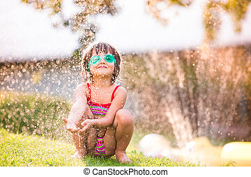 Cute girl crouching under the water splashing from sprinkler...