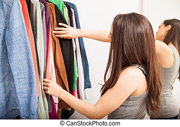 Young brunette deciding what to wear - Profile view of a...