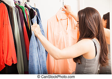 Pretty girl choosing what to wear - Profile view of a young...