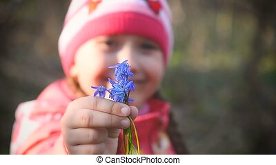 Girl holding a blue snowdrops - Girl in the spring wood in...