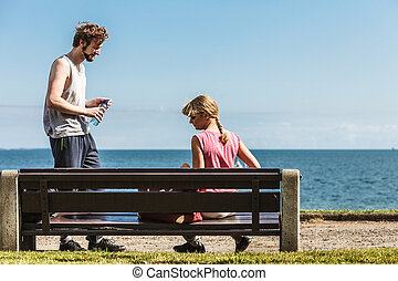 Woman and man with bottle of water outdoor Young couple...