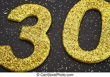 Number thirty yellow color over a black background....