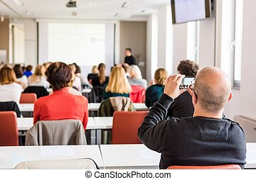 Audience at a business conference. Person taking photo with...