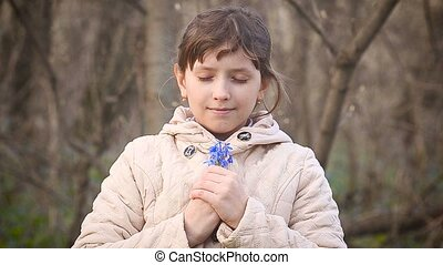 Girl collects blue snowdrops in the forest - Beautiful teen...